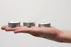 Three candles on a hand Royalty Free Stock Photography