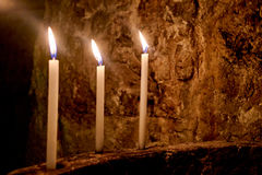 Three Candles in Line. Background stone wall Stock Photo