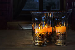 Three candles with ornaments in a glass holders Stock Photos