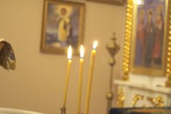 Three candles in Orthodox Church. The traditional rite of baptism. stock photo