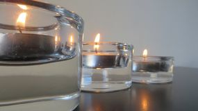 Three candles on perspective Stock Images