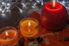Three candles on a red background. Two orange and one red candles, almonds and spices on a red paper background. They are illuminated by white lights Stock Photos