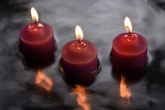 Three candles reflecting in water. HD 6000x4000. This image is a long exposure of  three candles reflecting in water Stock Photo