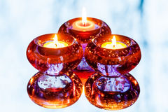 Three candles and reflection in the mirror. Three burning candles in round purple candlesticks are reflected in a mirror Royalty Free Stock Images