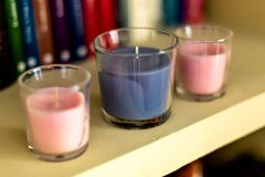 Three candles on shelf with background books royalty free stock photography