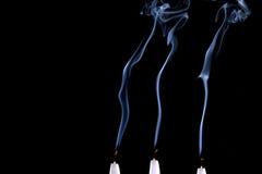 Three candles. Smoke dark black stock image