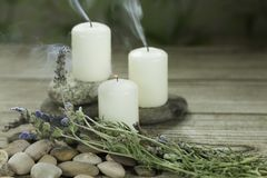 Three candles on river pebbles with lavender on wooden table and herbal background. Three candles with smoke on river pebbles with lavender on wooden table and royalty free stock image