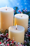 Three candles with snowfall Royalty Free Stock Photography