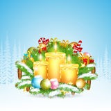 Three candles stand on snowy fir tree branches with presents. Christmas glossy element on forest background. Three candles stand on snowy fir tree branches with Stock Photo
