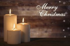 Three candles on table with Merry Christmas text royalty free stock photography