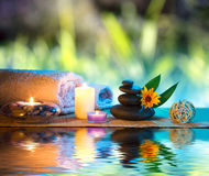 Three candles and towels black stones and orange daisy on water. For massage Stock Image
