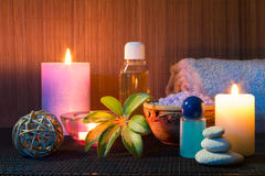 Three candles , towels , salt, oil and stones. For massage royalty free stock photo