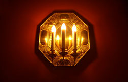 Three candles on a wall. A three decorative electric candles Royalty Free Stock Images