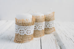 Three candles on white table. Three candles in rustic style, with lace on a white table Royalty Free Stock Photography