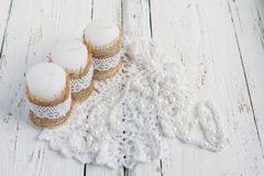 Three candles on white table. Three candles in rustic style, with lace on a white table Royalty Free Stock Image
