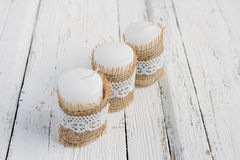 Three candles on white table. Three candles in rustic style, with lace on a white table Stock Photo