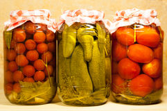 Three Canned Fresh Vegetables. Tomatoes Cherry, Cucumbers And Tomatoes In Big Glass Jar On Beige Background stock images