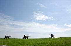 Three canons. Green grass and a blue sky Stock Photo