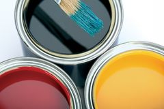 Three cans of paint and brush. stock photography