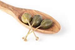 Three Capers in a Wooden Spoon Stock Images