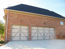 Three Car Garage. Two garage doors on the side of a modern american brick home with space to park three cars Royalty Free Stock Photography