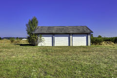 Three car garage with tile roof. Countryside landscape Stock Image