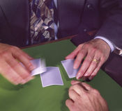 Three card monte. Man in jacket and tie dealing three card monte royalty free stock images