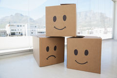 Three cardboard boxes with smiley signs against window Royalty Free Stock Photos