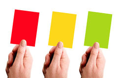 Three Cards. Red, yellow and green cards held by hand over a white background stock photography