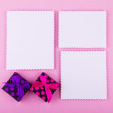 Three cards and gift boxes on pink background Royalty Free Stock Image