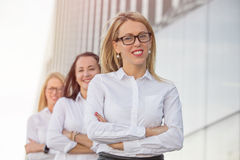 Three career women standing with crossed hands Stock Photo