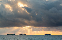 Three cargo freight ships on horizon. Three cargo or freight ships on horizon at sunset on cloudy stormy evening Royalty Free Stock Images