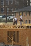 Three carpenters. Carpenters cutting  and nailing boards on second story of new apartment complex for nearby collage Royalty Free Stock Images