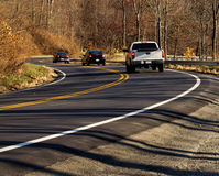 Three cars on a curvy road Royalty Free Stock Image