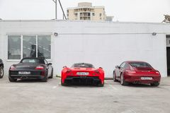 Three cars Marussia Motors model B1, Porsche Boxster and Carrera in red and black color on parking. Novosibirsk, Russia - 07.17.2019: Three cars Marussia Motors stock photography