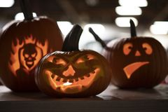 Three carved Halloween pumpkins on display