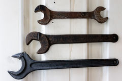 Three cast iron wrenches. Close up view on three cast iron wrenches in various states of rusting and wear attached to white metal wall Royalty Free Stock Image