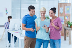 Three casual colleagues using digital tablet. In the office Stock Photography