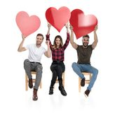 Three casual people with hands in the air celebrating love royalty free stock image