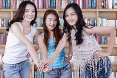 Three casual student joining hands Stock Photo
