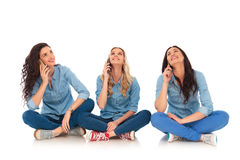 Three casual women talking on the phone and look up. While sitting on the floor Stock Photos