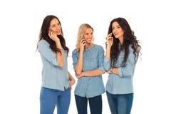 Three casual women talking on the phone. On white studio background Royalty Free Stock Photos