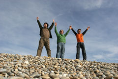Three casual young men at the beach. With arms wide open stock images