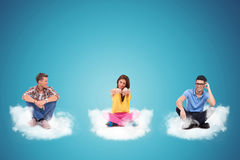 Three casual young people sitting on clouds Royalty Free Stock Photography