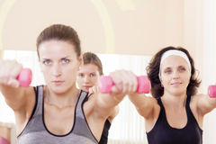 Three Caucaisan Fitness Girls Having a Workout With Barbells Indoors. Stock Photography