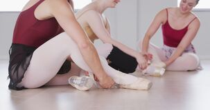 Caucasian ballet female dancers sitting together on the floor and chatting while tying ballet shoes