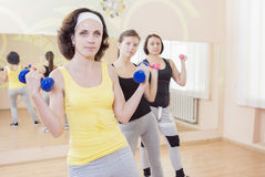 Three Caucasian Females Having a Workout Training with Barbells Indoors. Horizontal Image Orientation Stock Image