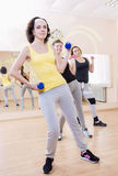 Three Caucasian Females Having a Workout Training with Barbells. Indoors. Vertical Image Orientation Stock Photo