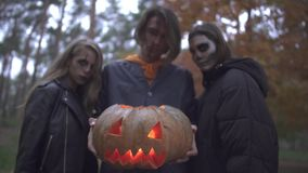 Three caucasian friends with horrifying halloween make-up stand in the autumn park in the evening. Tall brunette guy stock video
