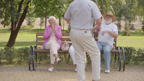 Three caucasian seniors sitting at the bench and applauding their cheerful male friend dancing. Elderly company having